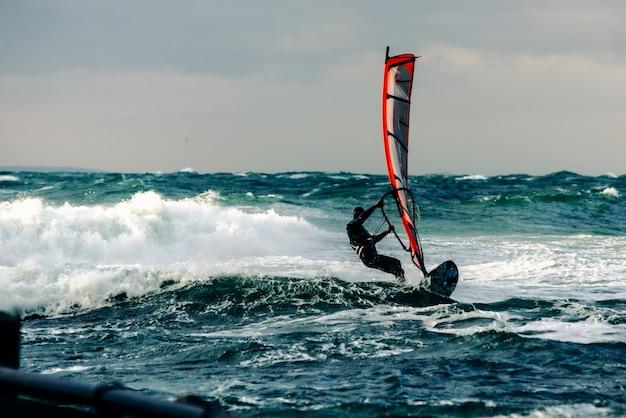 Praticare il surfing in un mare in tempesta al largo della costa di anapa, territorio di krasnodar. in russia, questo posto è una mecca definitiva per gli atleti.