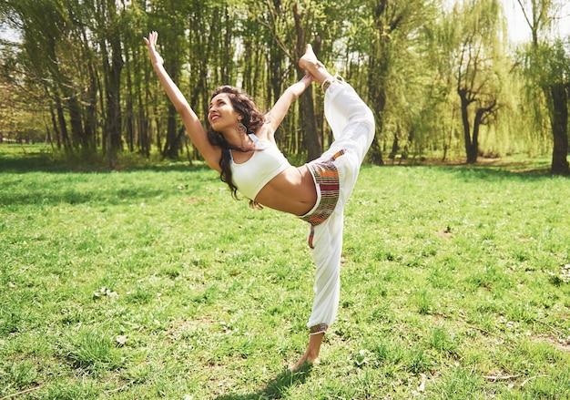 Praticare lo yoga di una bella ragazza al mattino sulle erbe sotto le parole del sole.