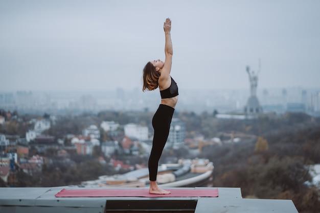 Praticare yoga donna sul tappetino sul tetto e fare esercizi di yoga
