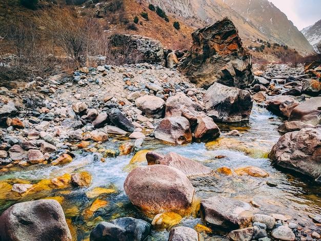 Prato di montagna con pietre accatastate muscose e piccolo fiume in primavera