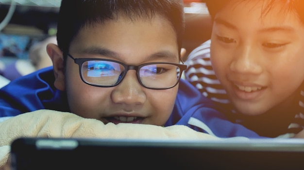 Preadolescenti asiatici che guardano su tablet pc, volto di sorriso.