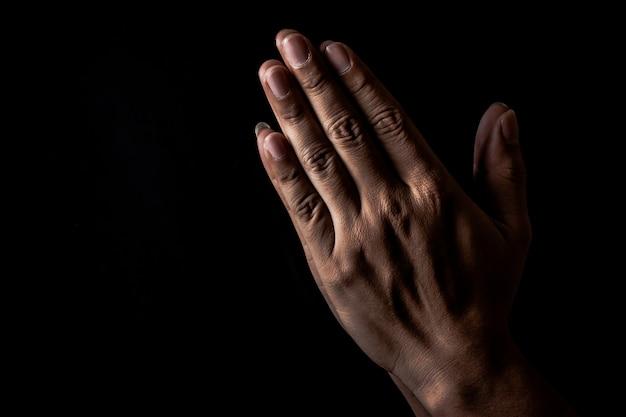 Pregando la mano a dio per soddisfare la propria speranza su sfondo nero, pregare a mano offrendo rispetto a dio