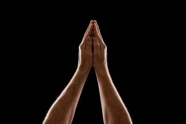 Preghiera del primo piano delle mani dell'uomo isolata su fondo nero.