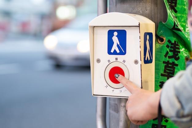 Premendo il pulsante per la persona disabile per attraversare la strada al semaforo
