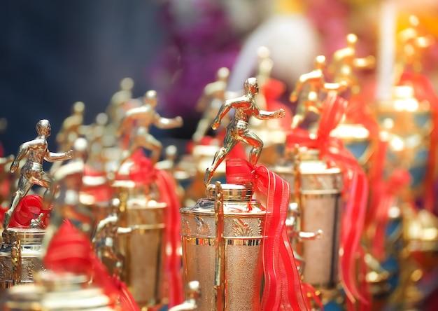 Premi della tazza del trofeo degli atleti con un nastro rosso.