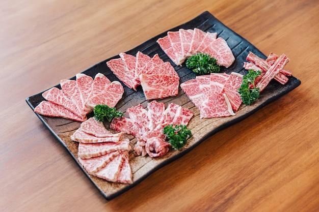 Premium rare affetta molte parti di manzo wagyu con texture marmorizzata su lastra di pietra servita per yakiniku, carne alla griglia.