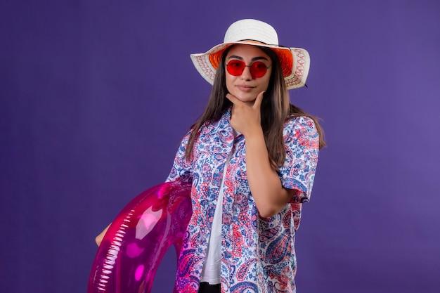 Premurosa bella donna che indossa un cappello estivo e occhiali da sole rossi tenendo l'anello gonfiabile guardando la fotocamera in piedi con la mano sul mento pensando isolato su sfondo viola