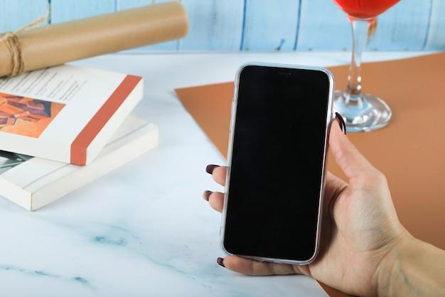 Prendendo uno smartphone nero nella mano sul tavolo