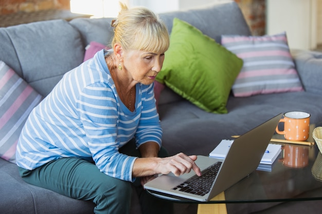 Prendere appunti durante la lezione. senior donna che studia a casa, ottenendo corsi online