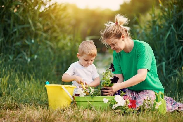 Prendersi cura della natura. madre e figlio che piantano piantina in terra su assegnazione sulla sponda del fiume. concetto di botanica ed ecologia.