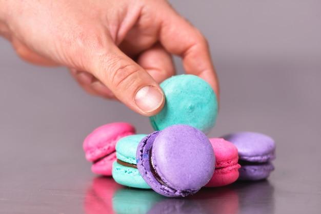 Prendi la mano raccogliendo un macaron sul tavolo