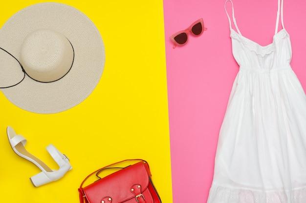Prendisole bianche, borsa rossa, scarpe bianche e occhiali da sole