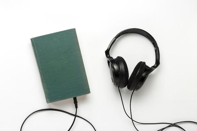 Prenota con una copertina blu e cuffie nere su sfondo bianco. concetto di audiolibri e apprendimento a distanza. vista piana, vista dall'alto