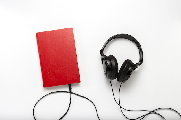 Prenota con una copertina rossa e cuffie nere su sfondo bianco. concetto di audiolibri e apprendimento a distanza. vista piana, vista dall'alto