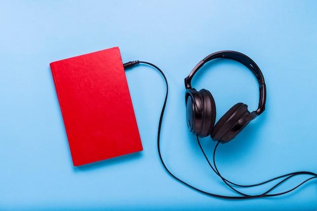 Prenota con una copertina rossa e cuffie nere su sfondo blu. concetto di audiolibri, autoeducazione. vista piana, vista dall'alto