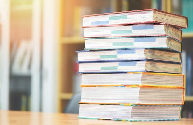 Prenota il concetto di istruzione di nuovo a scuola e studia - libri impilati in biblioteca sul tavolo