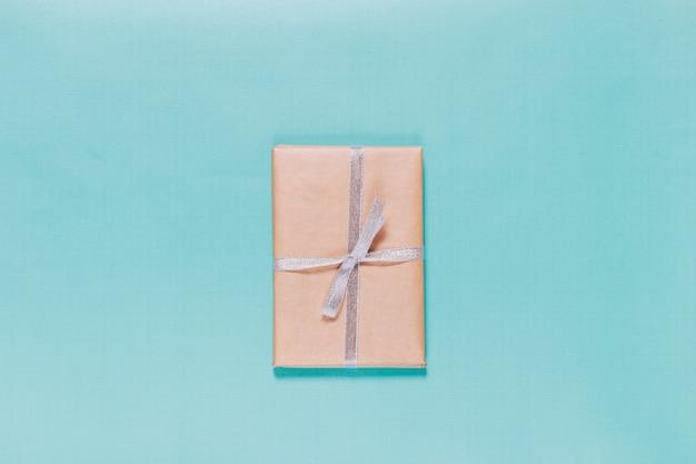 Prenota in carta da imballaggio con un nastro su uno sfondo blu
