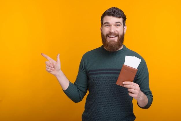 Prenota qui il tuo viaggio. il giovane sta indicando da parte mentre tiene il passaporto e i biglietti.