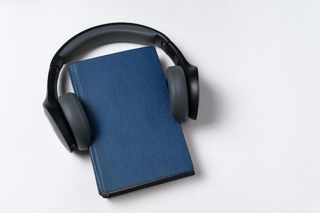 Prenota su sfondo bianco con le cuffie. concetto di letteratura audio. copia spazio vista dall'alto