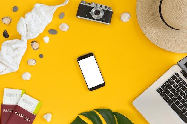 Prenotazione e pagamento concetto online di viaggio, vista dall'alto, piatto lay. telefono cellulare con schermo bianco vicino al computer portatile, vista dall'alto del desktop con accessori per viaggiatori