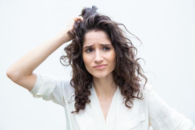 Preoccupato donna pensosa grattando la testa