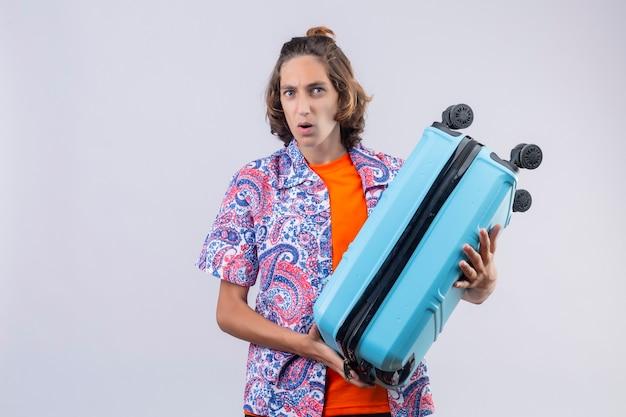 Preoccupato giovane bel ragazzo che tiene la valigia di viaggio che sembra sorpreso in piedi su sfondo bianco