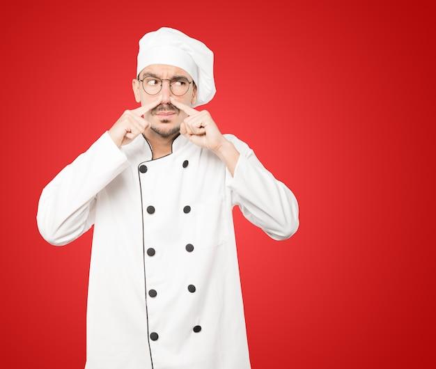Preoccupato giovane chef con un gesto di disgusto