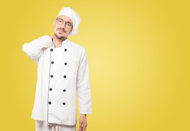 Preoccupato giovane chef con un gesto di dolore