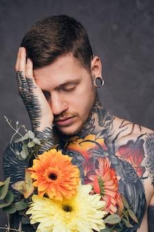 Preoccupato giovane tatuato con naso e piercing all'orecchio tenendo in mano il fiore