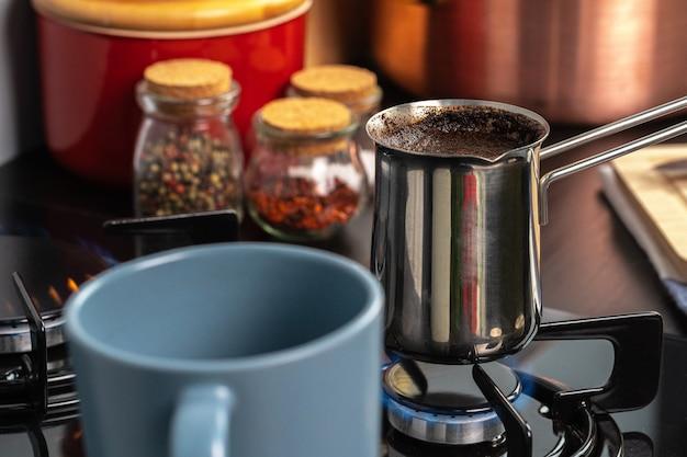 Prepara il caffè in un tacchino d'acciaio su una stufa a gas