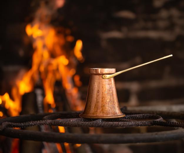 Prepara il caffè in un turco sul fuoco aperto.