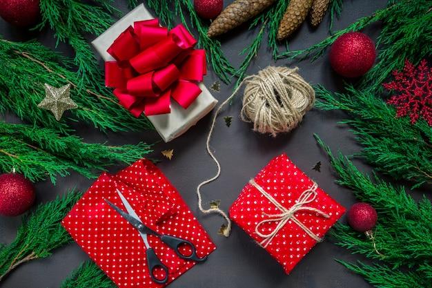 Preparando per la festa, avvolgendo i regali alle mani albero di candela degli accessori di natale
