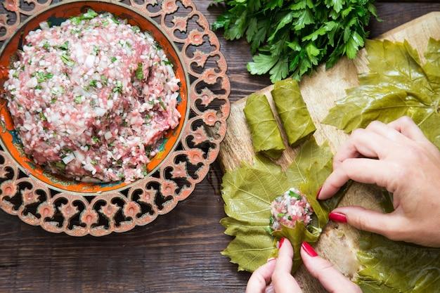 Preparare foglie di vite ripiene con riso e carne o dolma tradizionale. vista dall'alto