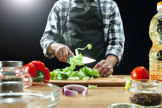 Preparare l'insalata. cuoco unico femminile che taglia le verdure fresche. processo di cottura. messa a fuoco selettiva. il cibo sano, cucina, insalata, dieta, concetto biologico di cucina
