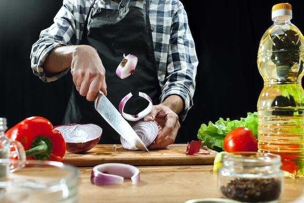 Preparare l'insalata. cuoco unico femminile che taglia le verdure fresche. processo di cottura. messa a fuoco selettiva