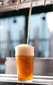 Preparare un bicchiere di birra da un rubinetto in un pub