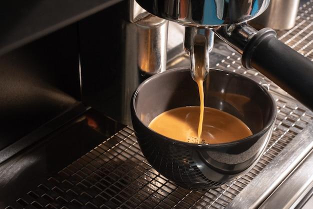 Preparare un espresso fresco nella macchinetta del caffè. la macchina da caffè produce caffè