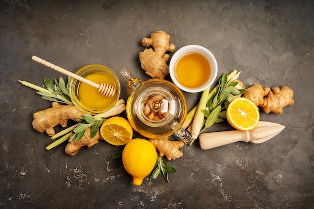 Preparare un tè antiossidante e antinfiammatorio sano con zenzero fresco, citronella, salvia, miele e limone su sfondo scuro con spazio di copia. vista dall'alto.