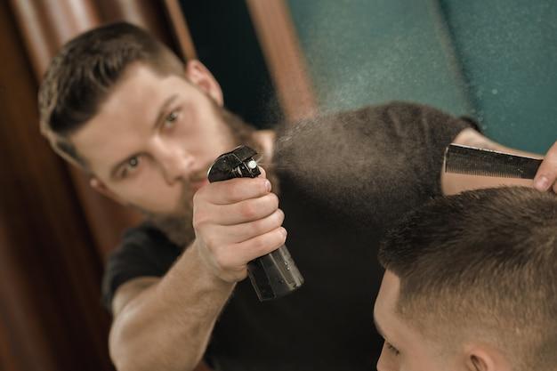 Prepararsi per il taglio di capelli. colpo del primo piano di un barbiere che spruzza acqua sui capelli del suo cliente prima di dare un taglio di capelli