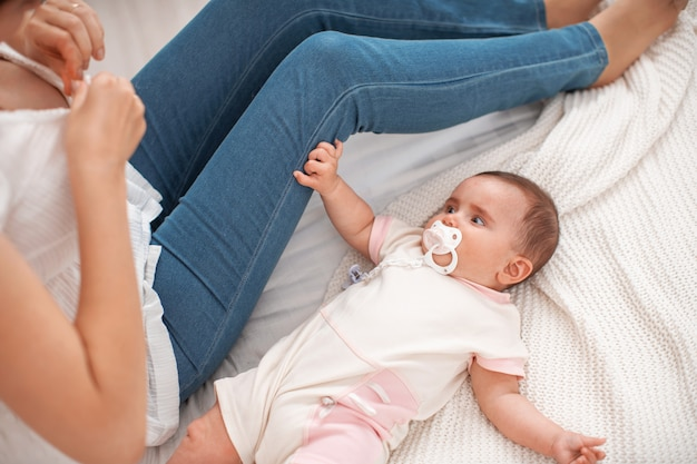Prepararsi per l'allattamento. il bambino è sdraiato sul letto e sta aspettando il tempo per l'alimentazione.