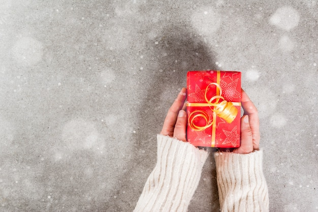 Prepararsi per le vacanze, natale. le mani femminili nella foto in un maglione caldo tengono un regalo in un involucro rosso con un nastro dorato. grigio, effetto neve, copyspace vista dall'alto