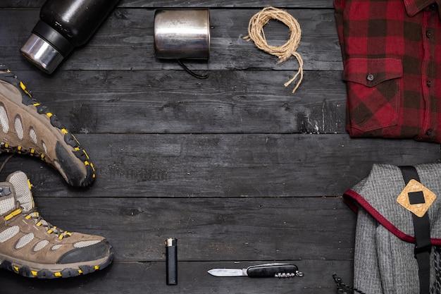 Prepararsi per un'escursione: zaino in spalla e vestiti distesi. vista dall'alto di scarponcini da trekking, zaino turistico e accessori da campeggio su sfondo nero