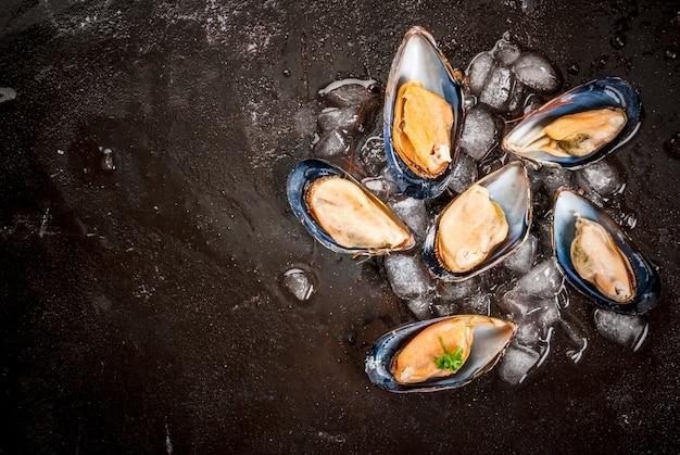 Preparato per cucinare la cena a base di pesce - cozze fresche aperte su ghiaccio, sul tavolo di cemento nero, con limone e condimenti. vista dall'alto, copia spazio