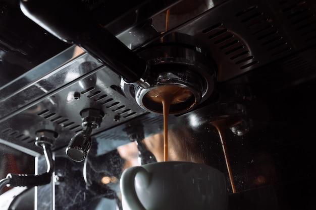 Preparazione del caffè espresso. il caffè viene versato dalla macchina del caffè nella tazza.