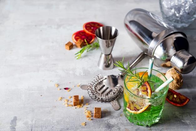 Preparazione del cocktail mojito. menta, lime, vetro, ghiaccio, ingredienti e shaker