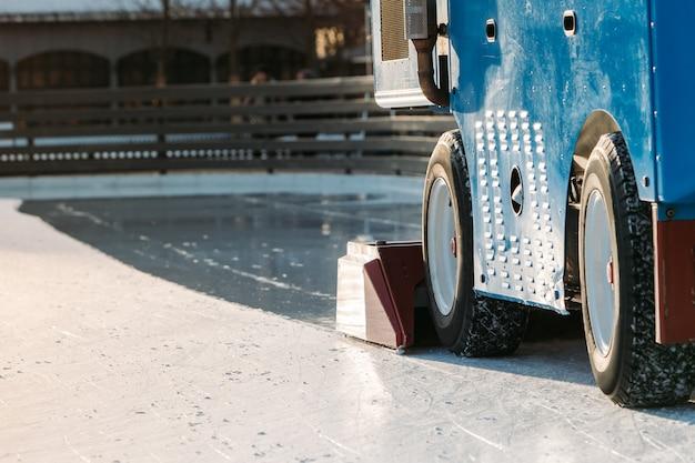 Preparazione del ghiaccio presso la pista di pattinaggio pubblica tra le sessioni del giorno di sole invernale. primo piano della macchina di manutenzione del ghiaccio