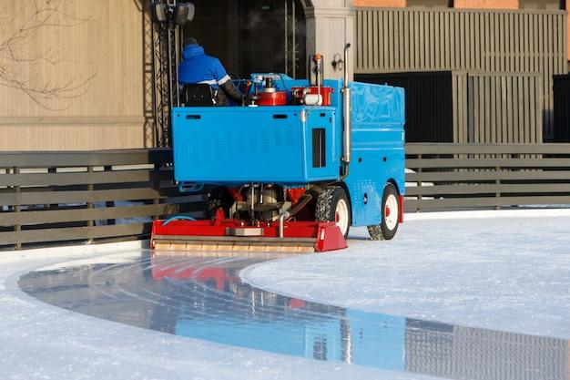 Preparazione del ghiaccio sulla pista tra le sessioni nella soleggiata giornata invernale / ghiaccio lucido pronto per la partita