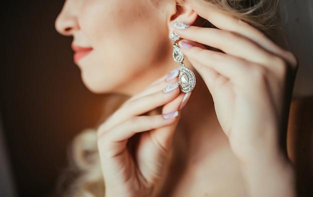 Preparazione del matrimonio bella, felice sposa abiti orecchini prima del matrimonio.