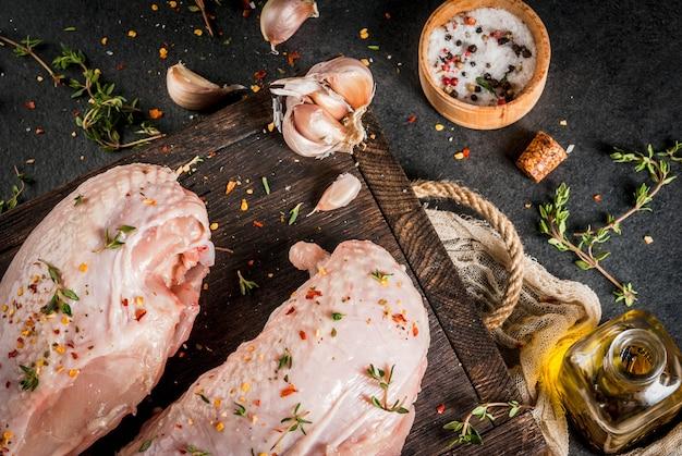 Preparazione del pranzo di cibo carne filetto di pollo con la pelle cruda su un tagliere con spezie timo aglio olio d'oliva sale pepe tavola di legno sfondo nero pietra