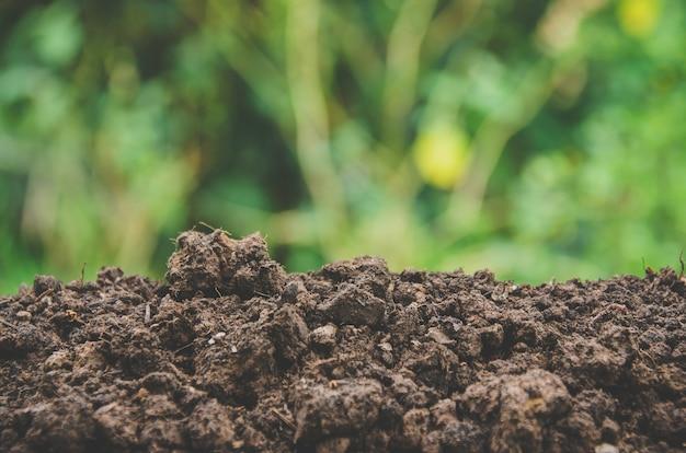 Preparazione del terreno per l'agricoltura e mucchio di terreno con sfondo verde.